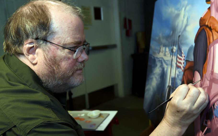 Morgan Wilbur, an artist with the Navy's Combat Art Program, paints a scene from his 2014 deployment aboard the guided-missile destroyer USS Mustin, Dec. 28, 2016.