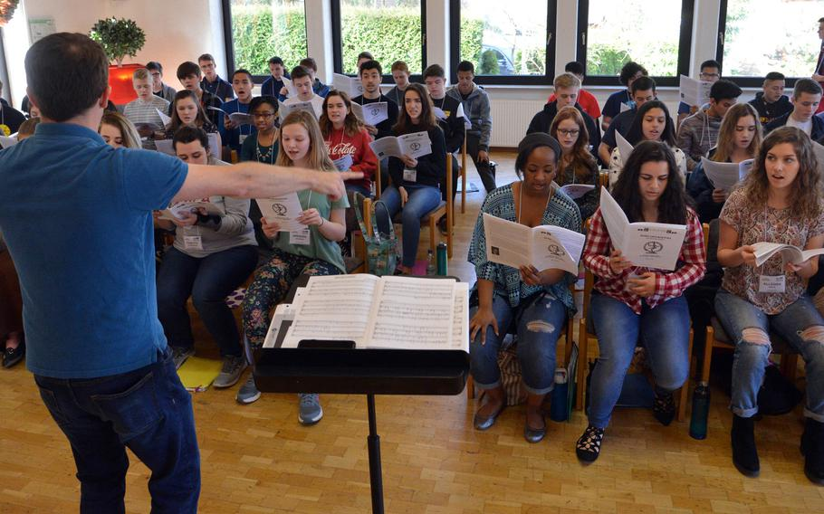 Ryan Holder directs the choir at the DODEA-Europe Honors Music Festival, Tuesday, March 14, 2017.