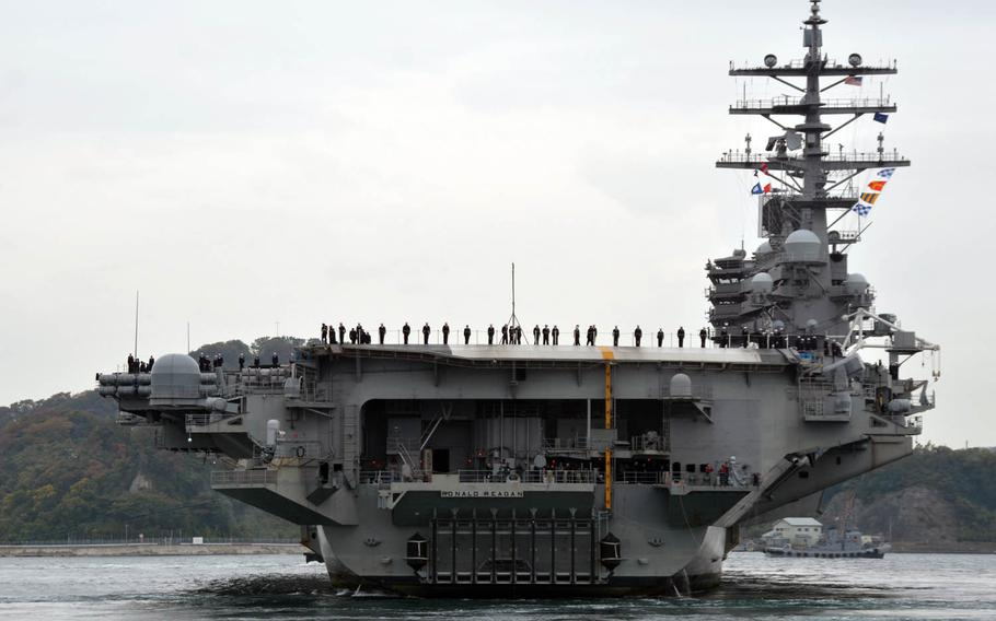Sailors man the rails on board the aircraft carrier USS Ronald Reagan as it returns to Yokosuka Naval Base, Japan, in November.