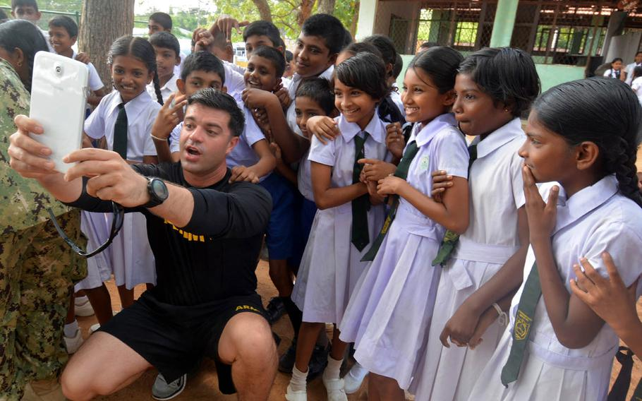 Sgt. 1st Class David Matthews, based at Fort Bragg, N.C., takes a selfie with children at a school on Sri Lanka's rural south coast during the Pacific Partnership 2017 exercise, March 7, 2017.