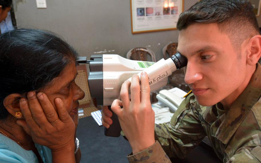 Sgt. Jorge Laguna-Ramos examines a patient's eyes at a hospital in Hambantota, Sri Lanka, March 8, 2017. Ramos and health care providers from the Army and Navy saw hundreds of patients as part of Pacific Partnership 2017, a three-nation humanitarian exercise.