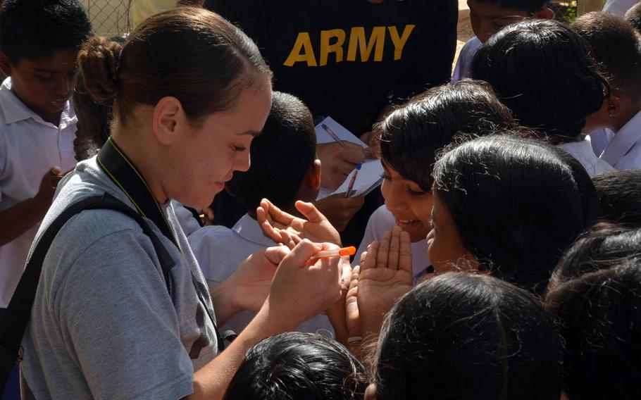 Army Staff Sgt. Monet Figueroa signs autographs on hands, notebooks and anything alse the children request at a school on Sri Lanka's rural south coast during the Pacific Partnership 2017 exercise, March 7, 2017.