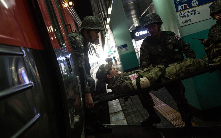 South Korean medics evacuate a simulated U.S. Army casualty at a train station in Suwon, South Korea, Wednesday, March 15, 2017.