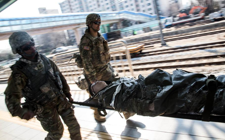 American soldiers rush a simulated casualty to a medical train in Seoul, South Korea, Wednesday, March 15, 2017.