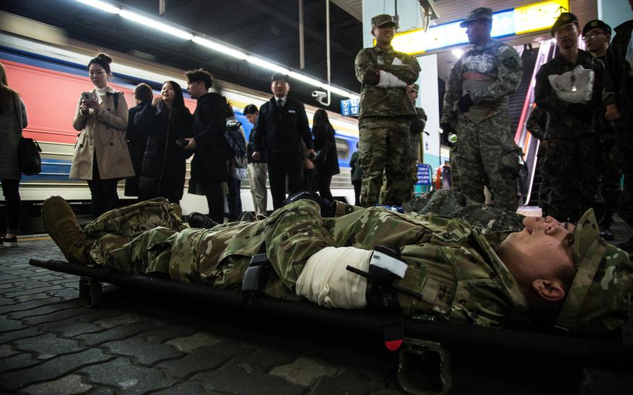 Simulated casualties wait to be evacuated during a drill Wednesday, March 15, 2017, in South Korea.