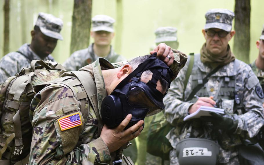 An instructor dons a gas mask during the Expert Field Medical Badge training at Grafenwoehr, Germany, on Monday, March 20, 2017. During the training, candidates from 11 nations had to perform 13 tasks ranging from chemical warfare defense to medical evacuation drills, in order to earn one of the most sought after badges in the U.S. Army.