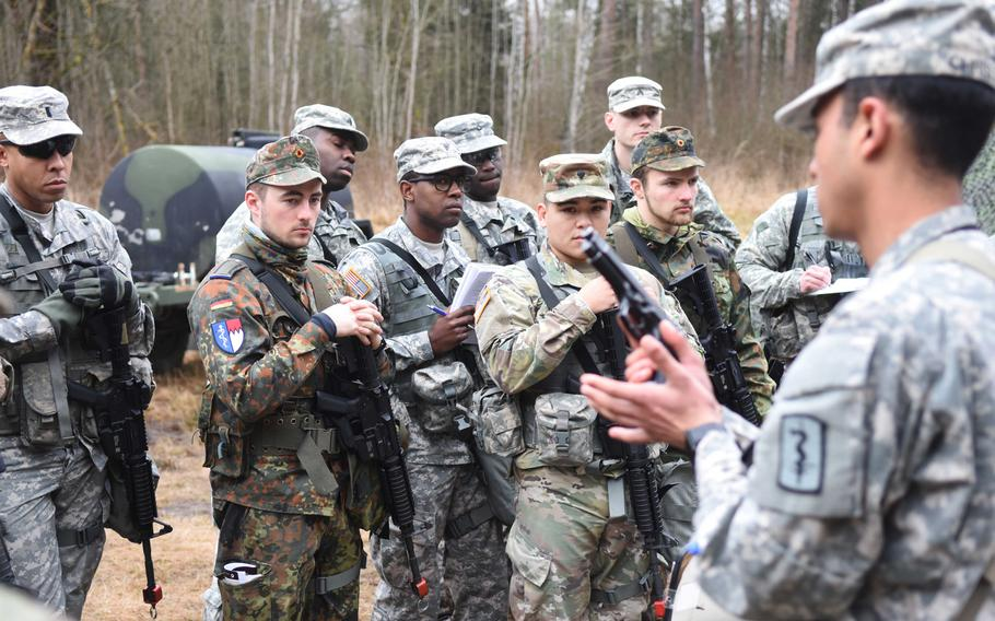 An instructor goes over the Beretta M9 pistol during the Expert Field Medical Badge training at Grafenwoehr, Germany, Monday, March 20. The candidates will need to know how to perform a function check on the pistol during the test, as it is standard issue for many combat medics.