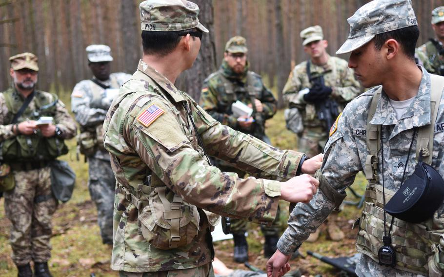 Instructors demonstrate how to tie a square knot to secure a patient to a stretcher during the Expert Field Medical Badge training at Grafenwoehr, Germany, Monday, March 20, 2017.