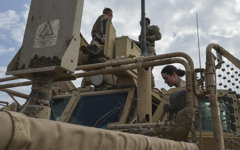 Pfc. Alexandria Campbell helps Sgt. Brandon Bush and Pfc. Shayne Jensen install a .50-caliber machine gun on the Common Remotely Operated Weapon Station atop a mine-resistant vehicle on Qayara Airfield West, Friday, March 17, 2017. Since March 2016, the military has been integrating women into many combat roles previously closed to women.