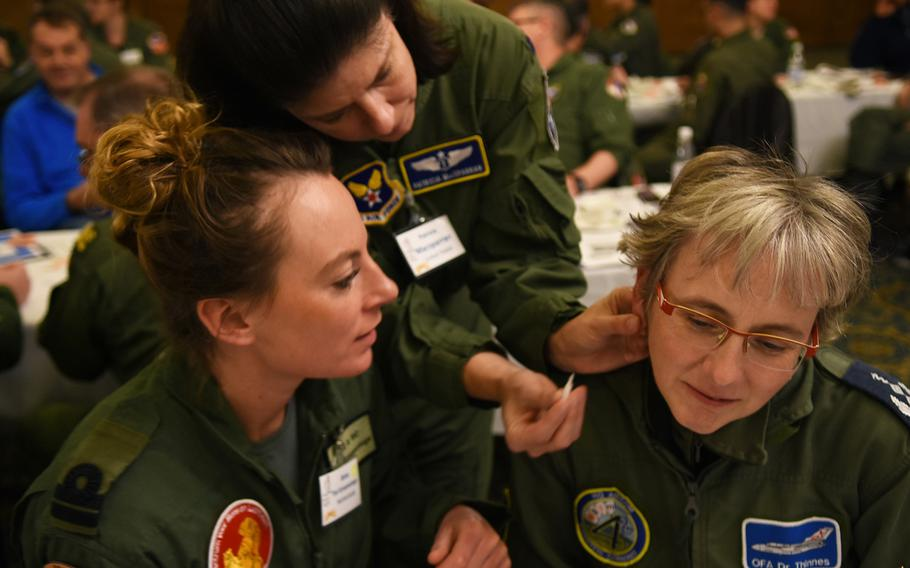 U.S. Air Force Lt. Col. Patricia Macsparran, center, shows Capt. Tiel Groenestege, a flight surgeon in the Royal Netherlands Navy, where to place the needle inserter on the ear of Lt. Col. Katrin Thinnes, right, an anesthesiologist and ICU specialist with the German Air Force. Macsparran, the aerospace medicine consultant to the Air Force surgeon general, was one of the presenters Tuesday, March 21, 2017, at a workshop on battlefield acupuncture during an international aerospace medicine conference at Ramstein Air Base, Germany.