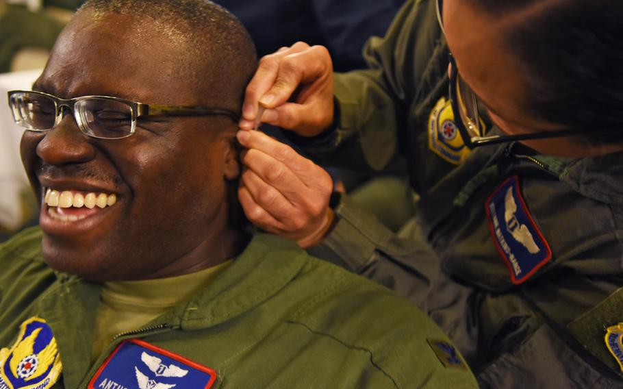Col. Anthony Mitchell grimaces while Lt. Col. Stefanie Watkins-Nance inserts a needle into his ear during a battlefield acupuncture workshop on Tuesday, March, 21, 2017, at Ramstein Air Base, Germany.