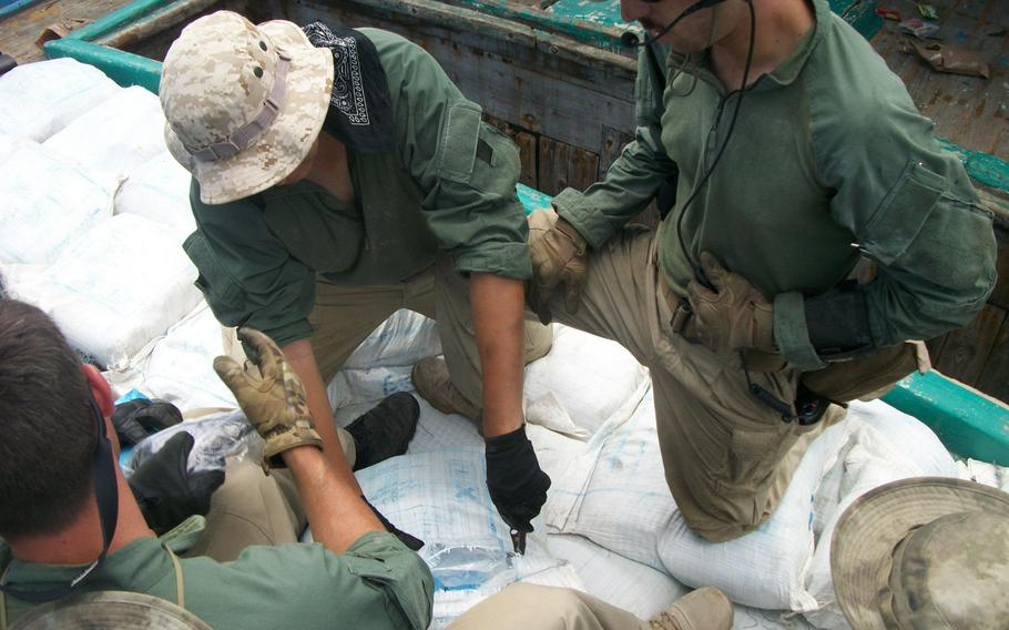 Sailors assigned to the USS Laboon inspect bags containing hashish during an inspection of a dhow in the Arabian Sea, Friday, March 17, 2017.