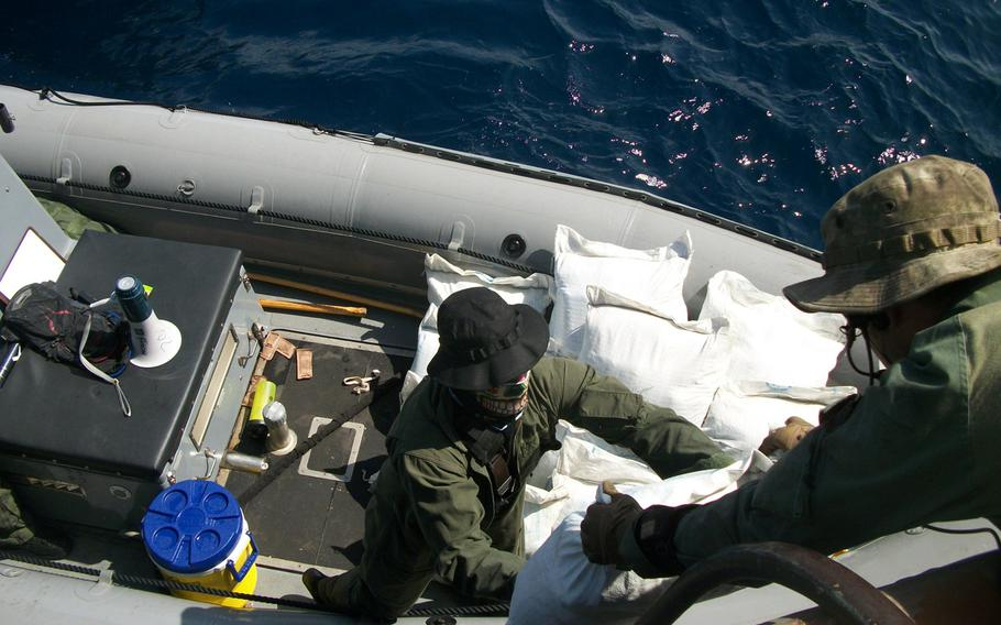 Sailors assigned to the USS Laboon offload bags containing hashish from a dhow in the Arabian Sea, Friday, March 17, 2017. Laboon sailors intercepted the dhow and seized 500 kg of hashish, their second successful drug interdiction operation in five days.