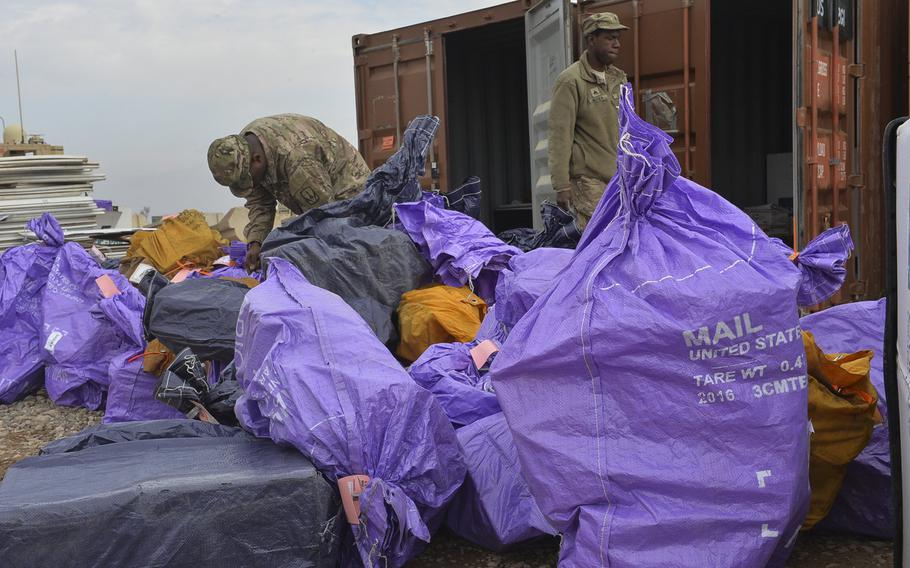 Sgt. Alvin Bethea Jr. walks past a pile of mailbags being sorted on Qayara Airfield West, March 17, 2017. Bethea, a soldier with the 678th Adjutant General Company Postal Platoon, said mail arrives about once every two weeks. Soldiers at the logistics hub about 40 miles south of Mosul say mail, especially care packages, is one of the few morale boosters here.