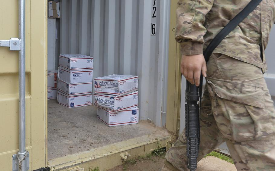 A soldier walks past stacks of care packages in a shipping container at Qayara Airfield West, Iraq, on March 17, 2017. Some of the packages, shipped through the nonprofit ''Adopt a Platoon,'' are sent by strangers in support of deployed troops who say they appreciate the small treats from home.