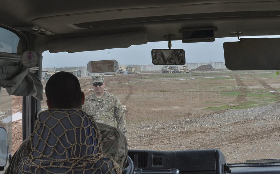Rain turns the powdery dirt of Qayara Airfield West, Iraq, into a muddy sludge, which bogged down a bus full of reporters on the base, March 17, 2017. Pictured here on that day, Lt. Col. Sebastian Pastor, the base commander, helps instruct a bus driver in how to get out of the mire.