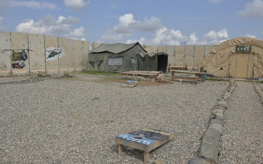 Pictured here are cornhole boards in a gravel lot in an area where arimen of the 370th Air Expeditionary Advisory Group detachment work on Qayara Airfield West, Iraq. As the base is being built up, planners struggle to balance the investment into the installation with the need to avoid ''frivolous'' niceities on a base destined to be returned to the Iraqi government.