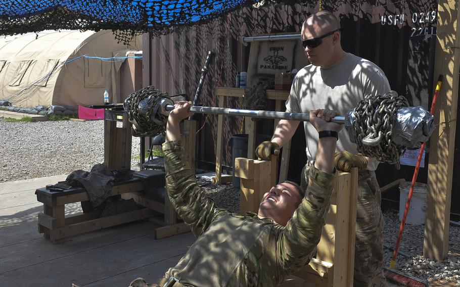 Senior Airman Troy Ondrey presses a makeshift barbell loaded with chains, about 135 pounds altogether, as Staff Sgt. Shawn Benton spots him in the 370th Air Expeditionary Advisory Group detachment's ''Iron Paradise'' gym on Qayara Airfield West, Iraq, March 17, 2017.