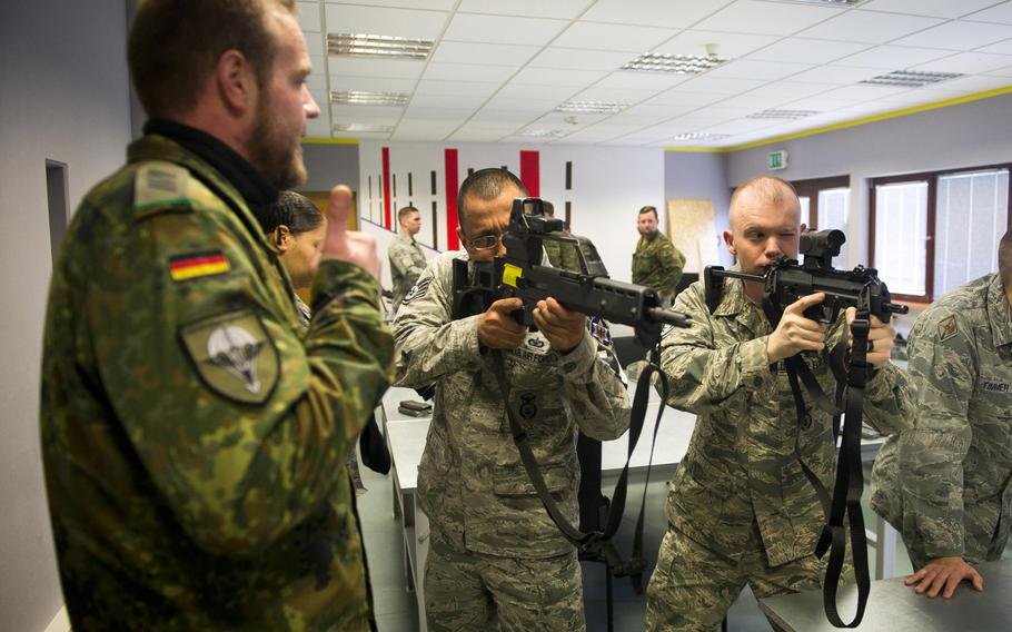 U.S. Air Force Staff Sgts. Caleb Bruce, right, and Manuel Amaya look through the sights of German army firearms as Cpl. Christopher Brings talks about the weapons in Kaiserslautern, Germany, on Thursday, March 23, 2017.