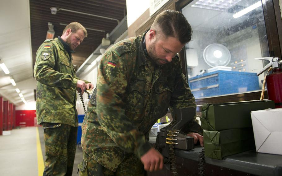 Cpls. Benedikt Dewald, right, and Christopher Brings load MG3 ammunition belts in Kaiserslautern, Germany, on Thursday, March 23, 2017.