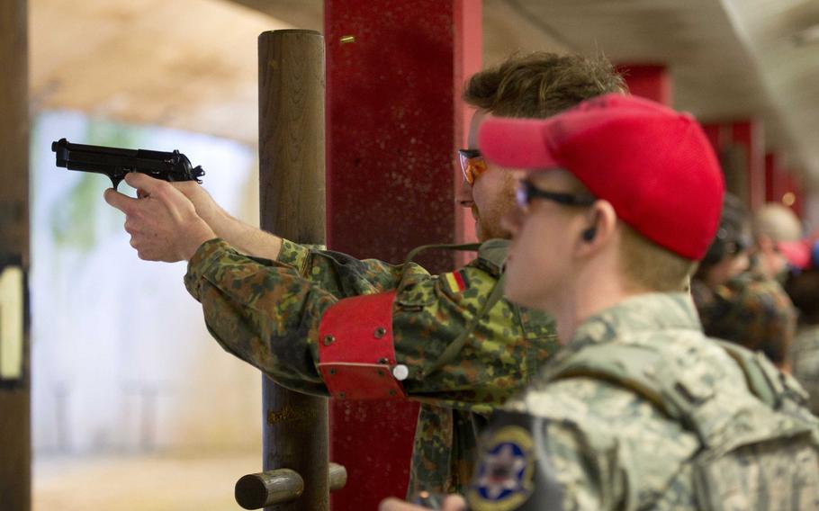 Cpl. Frederik Rosen, left, fires an M9 as Staff Sgt. Shane Fairchild watches in Kaiserslautern, Germany, on Thursday, March 23, 2017.