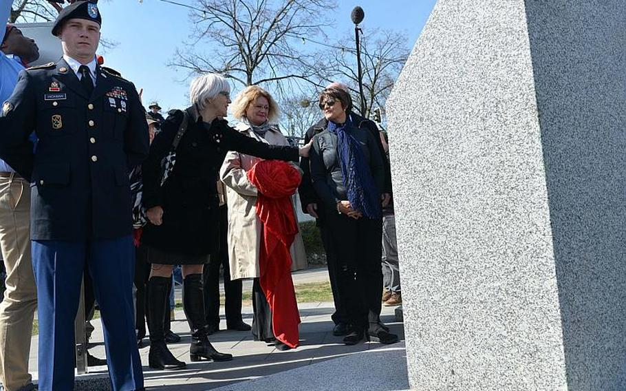Helen Patton, left, reaches out to touch Luci Schey after they and Catherine Rommel, center, unveiled a monument marking the World War II crossing of the Rhine River by American troops in 1945 at Nierstein, Germany, Saturday, March 25, 2017. Patton is the granddaughter of Gen. George S. Patton while Rommel is the granddaughter of Erwin Rommel, the famous German general. Schey's foundation was  responsible for raising much of the money to build the monument.