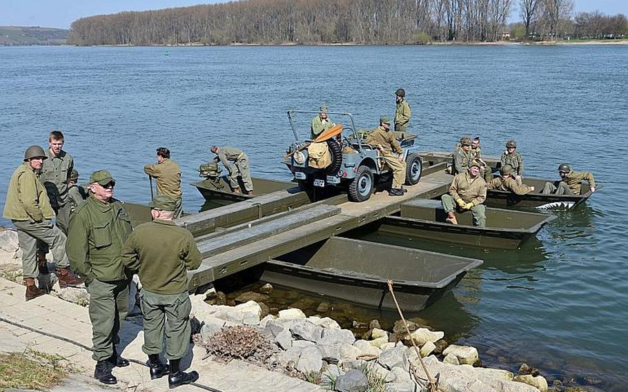 World War II re-enactors crossed the Rhine River in this vintage pontoon raft following the unveiling of the Rhine River crossing monument in Nierstein, Germany, Saturday, March 25, 2017.
