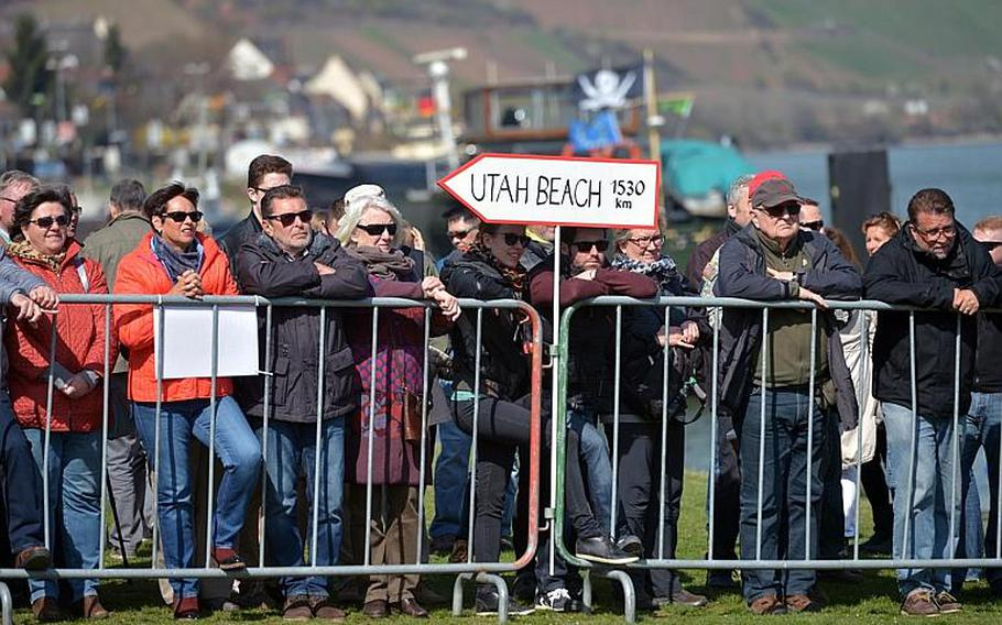 On the banks of the Rhine River, a sign points to Utah Beach, the D-Day landing beach, as people watch the unveiling ceremony of the dedication ceremony for the World War II Rhine River crossing monument in Nierstein, Germany, Saturday, March 25, 2017.