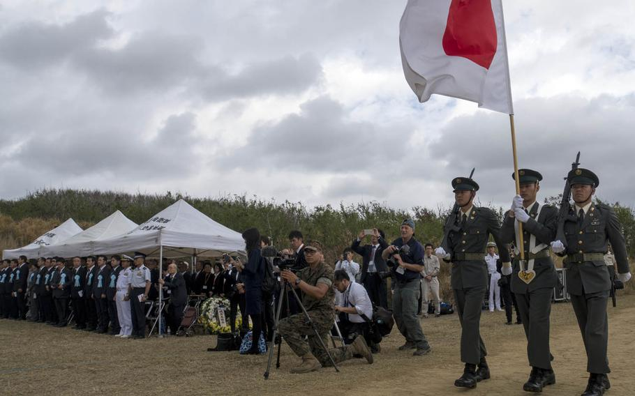 Japanese troops present the colors during a ceremony marking the 75th anniversary of the Battle of Iwo Jima, Saturday, March 25, 2017.