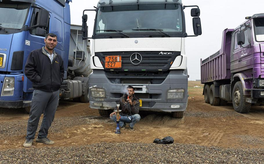 Iraqi drivers relax in front of their trucks, which brought tons of gravel to a coalition tactical base under construction south of Mosul, March 2, 2017.