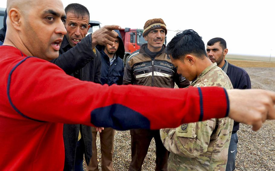 U.S. Army 1st  Lt. Adam Ward checks his notes as, left, Emaad Kudear, a contract linguist attached to the 2nd Battalion, 508th Infantry Regiment, passes on instructions to Iraqi truck drivers hauling gravel to a forward tactical base under construction south of Mosul, Iraq, March 2, 2017.