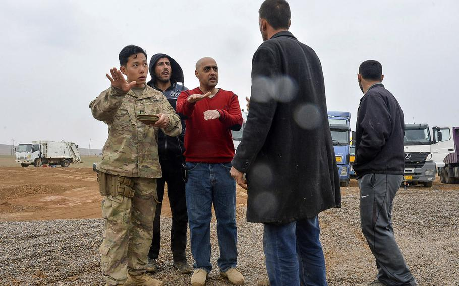 U.S. Army 1st Lt. Adam Ward gives instructions to a group of Iraqi truck drivers, aided translator Emaad Kudear, a contract linguist attached to the 2nd Battalion, 508th Infantry Regiment, at a coalition tactical base south of Mosul, Iraq, March 2, 2017.