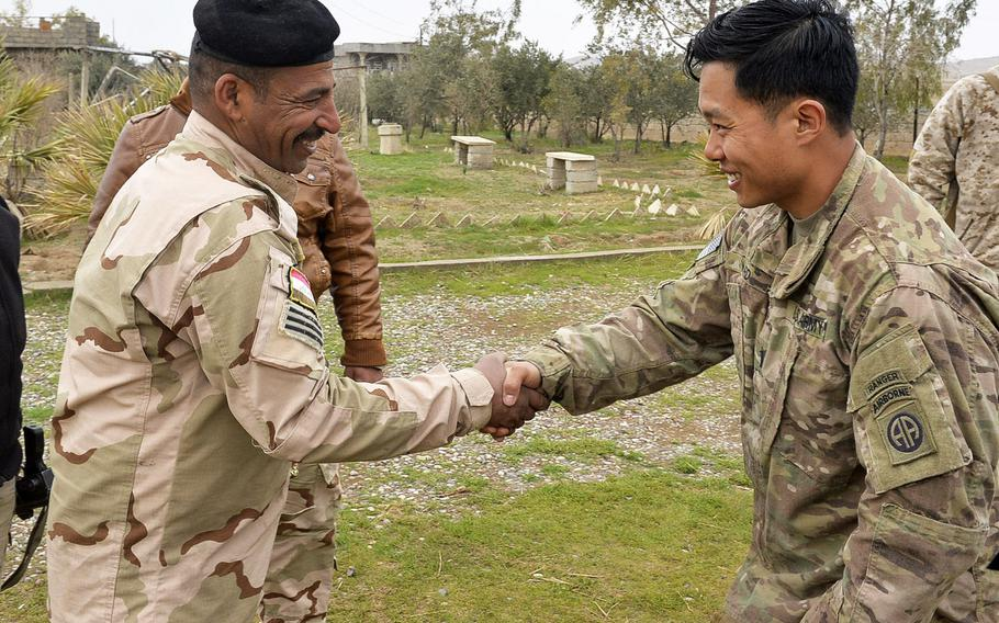 U.S. Army 1st Lt. Adam Ward shakes hands with an Iraqi counterpart during the construction of a coalition base south of Mosul on Thursday, March 2, 2017. Ward, an infantry officer, was leading the construction of the base near a cluster of houses on a mud-and-grass expanse.