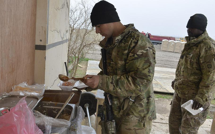 Spc. Humberto Cadena of Cookeville, Tenn., pours beans over his rice, part of a meal provided to U.S. advisers by the Iraqi army's 9th Amored Division, at a tactical base under construction south of Mosul, March 2, 2017.
