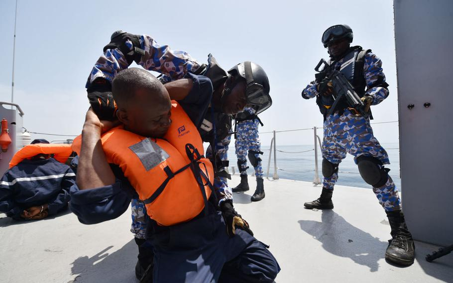 Sailors from the Ivory Coast search a role player in a search-and-seizure drill during the Obangame Express exercise, which brought together 32 nations to improve at-sea policing, Friday, March 24, 2017.