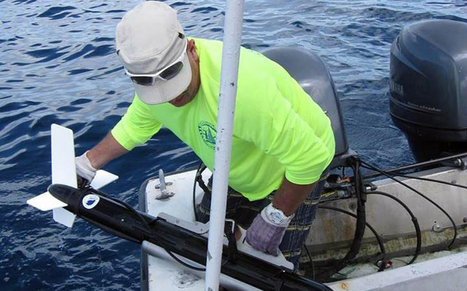 Tim Roberge of the Kwajalein MIA Project lifts a sonar into his boat after a search for missing World War II aircraft in the waters of the Kwajalein Lagoon, Marshall Islands.