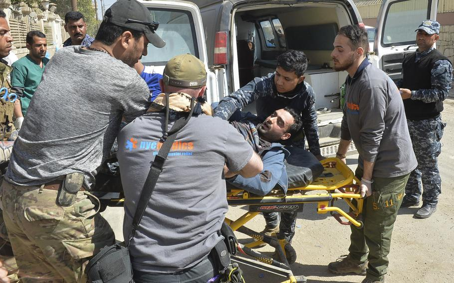 A wounded Iraqi federal police officer is carted to a medical station near the front lines of the battle for west Mosul, Iraq, March 9, 2017. Some of the attendants are volunteers with the New York-based organization NYC Medics, one of several groups partnered with the World Health Organization to help treat the casualties of the offensive in Mosul.