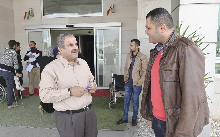 Avdal Wasman, left, a charge nurse at the West Irbil Emergency Hospital in Iraq, chats with Dr. Hazhem Mama, an orthopedic surgeon and administrator at the medical center.