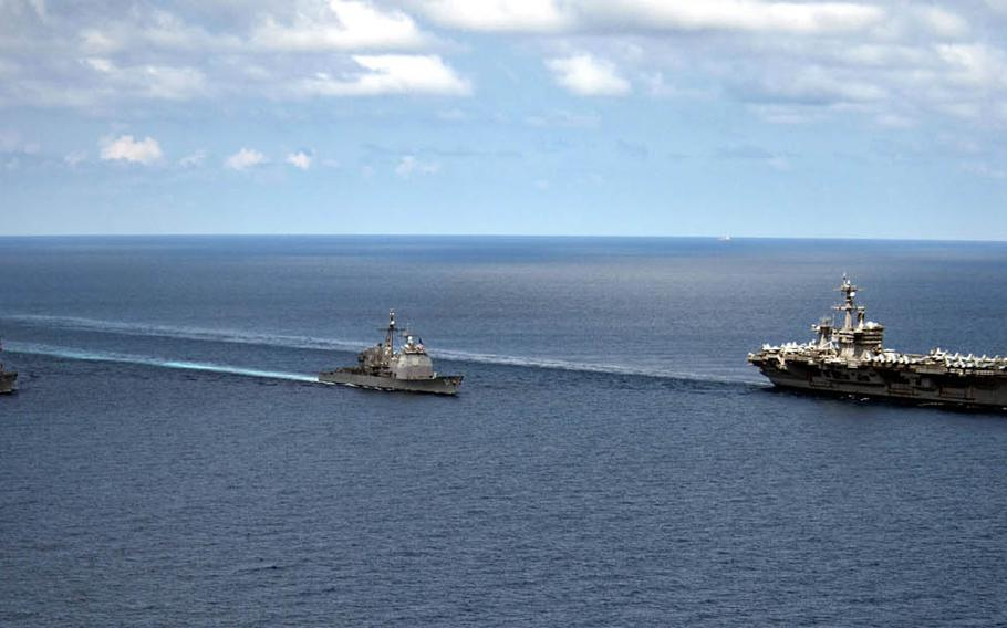The destroyer USS Michael Murphy, left, and the cruiser USS Lake Champlain are underway with the aircraft carrier USS Carl Vinson in waters near Indonesia, Friday, April 14, 2017.