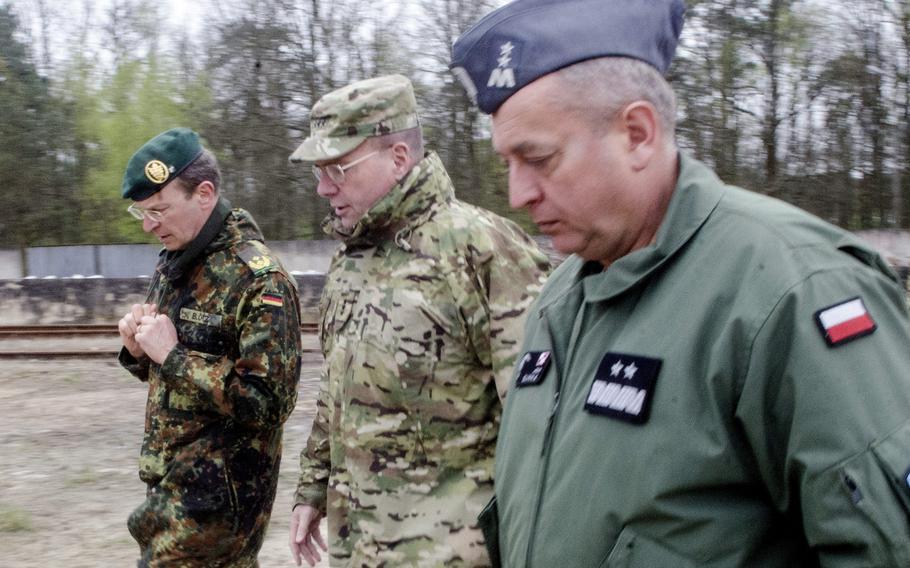 U.S. Army Europe commander Lt. Gen. Ben Hodges, center, walks with German Army Maj. Gen. Stefan Blotz, left, and Polish Maj. Gen. Jan Sliwka near the railhead at the Polish military base in Powidz, Wednesday, April 26, 2017.