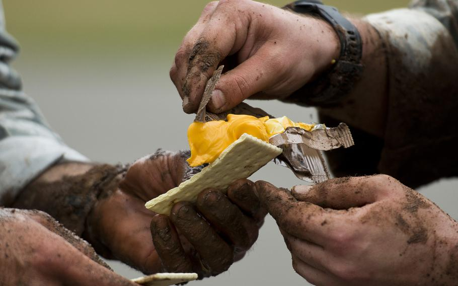 Senior Airman Ryan Daggett, right, and Staff Sgt. Jordan Lucey, from the 435th Security Forces Squadron, spread cheese on a cracker from a Meal Ready to Eat during the 435th Contingency Response Group Olympics at Ramstein Air Base, Germany, on Friday, May 5, 2017.