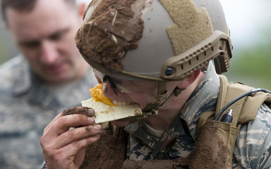Senior Airman Ryan Daggett, from the 435th Security Forces Squadron, eats cheese and a cracker from a Meal Ready to Eat during the 435th Contingency Response Group Olympics at Ramstein Air Base, Germany, on Friday, May 5, 2017.