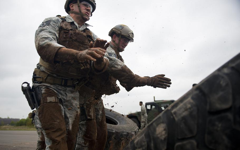 Staff Sgts. Jordan Lucey, left, and Jacob Van Dyke from the 435th Security Forces Squadron, flip a tire during the 435th Contingency Response Group Olympics at Ramstein Air Base, Germany, on Friday, May 5, 2017.