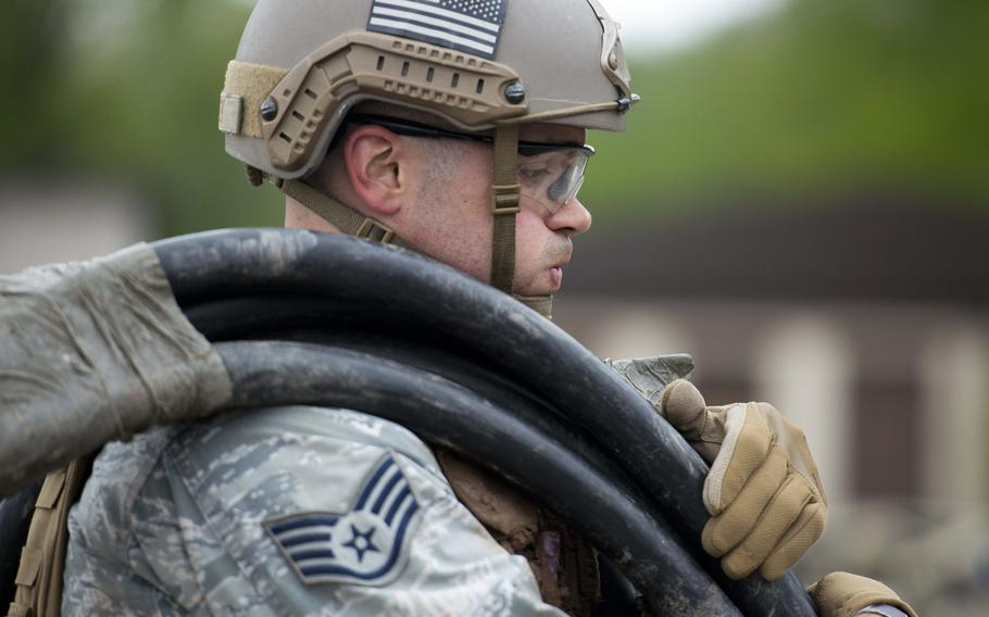 Staff Sgt. Jordan Lucey, from the 435th Security Forces Squadron, carries a roll of cable during the 435th Contingency Response Group Olympics at Ramstein Air Base, Germany, on Friday, May 5, 2017.