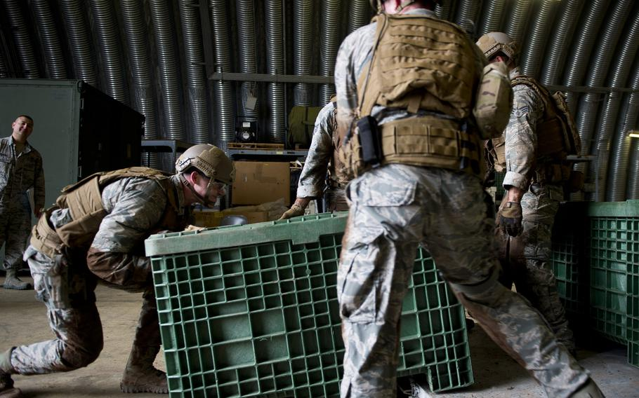 1st Lt. Jeffery Davis, left, from the 435th Security Forces Squadron, loads a container onto a pallet during the 435th Contingency Response Group Olympics at Ramstein Air Base, Germany, on Friday, May 5, 2017.