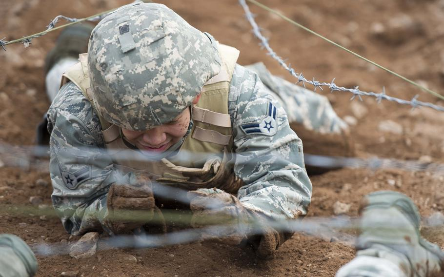 Airman 1st Class Arambulo Miles, from the 435th Construction and Training Squadron, crawls through the dirt during the 435th Contingency Response Group Olympics at Ramstein Air Base, Germany, on Friday, May 5, 2017.
