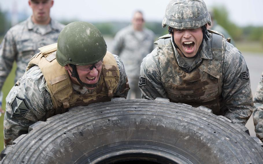 Staff Sgt. Adam Borjon, right, and Master Sgt. Robert Fitte, from the 435th Construction and Training Squadron, flip a tire during the 435th Contingency Response Group Olympics at Ramstein Air Base, Germany, on Friday, May 5, 2017.