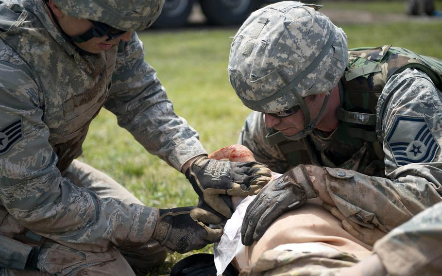 Master Sgt. David Thomas, right, and Staff Sgt. Adam Borjon from the 435th Construction and Training Squadron, treat a simulated patient during the 435th Contingency Response Group Olympics at Ramstein Air Base, Germany, on Friday, May 5, 2017.