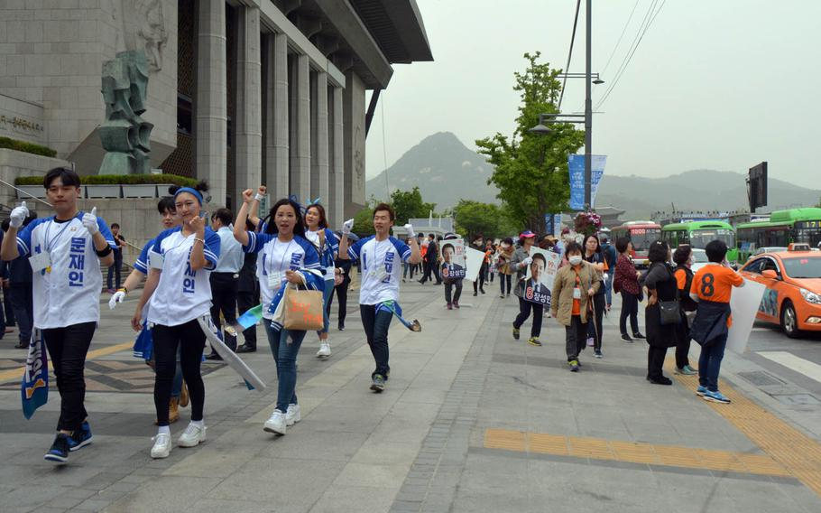 Supporters of South Korean presidential election front-runner Moon Jae-in (wearing blue and white) pass supporters of lesser-known candidate Chang Sung-min (wearing orange) as campaigns prepare for rallies in Seoul, Monday, May 8. 2017.