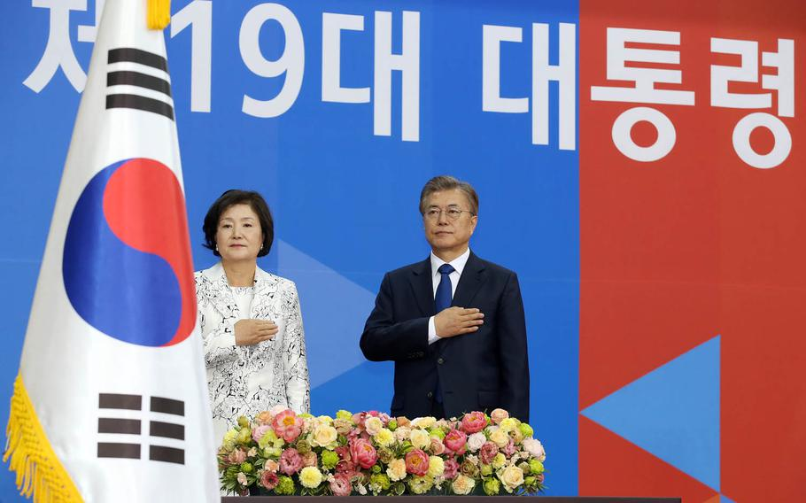 New South Korean President Moon Jae-in and his wife, Kim Jung-suk, observe the national anthem during his swearing-in ceremony in Seoul, Wednesday, May 10, 2017.